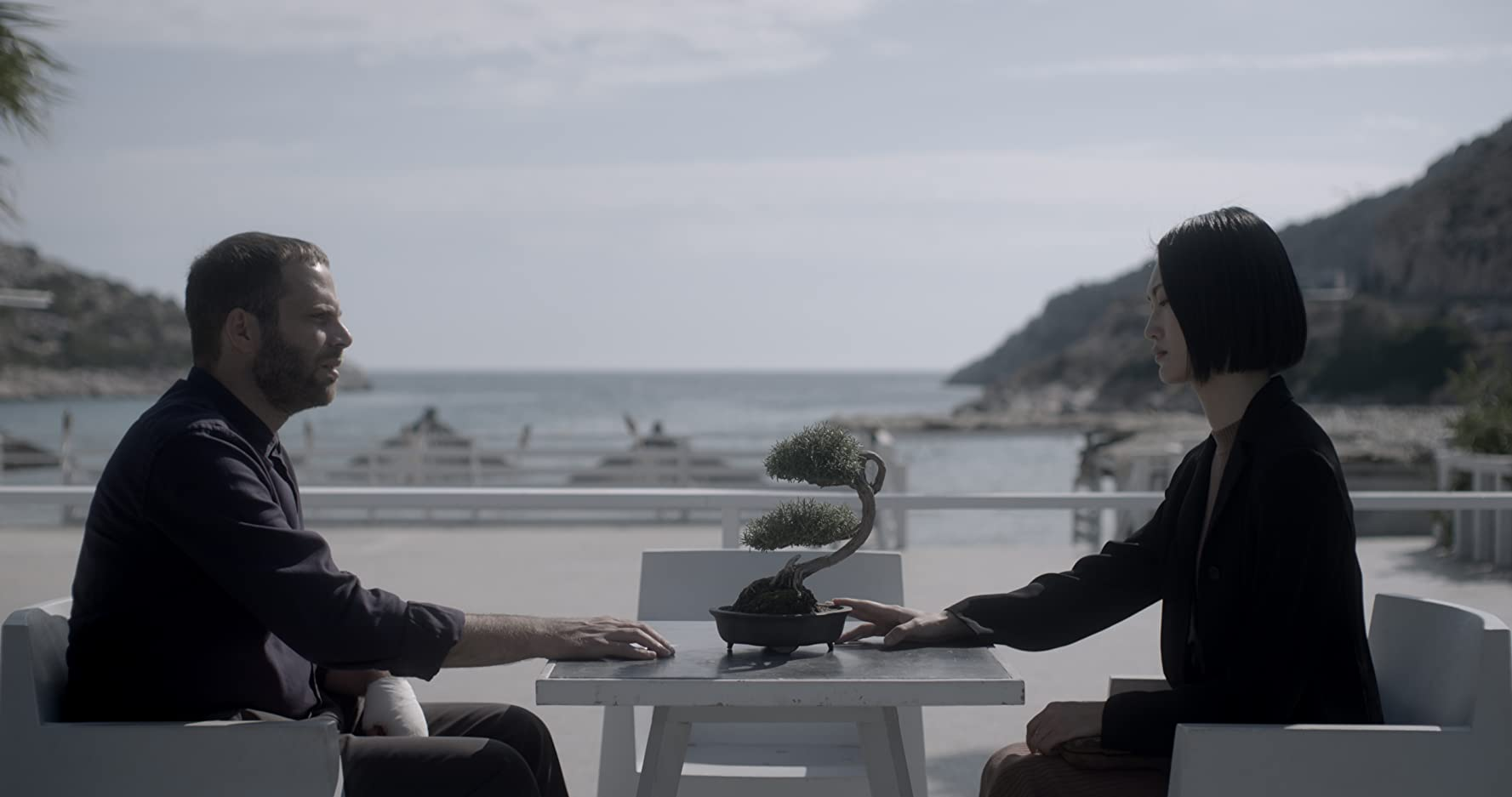 a guy and a girl sitting at a table film still unpleasant
