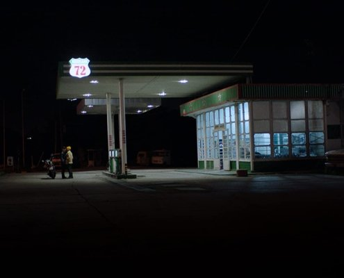 a gas station in the night film still the distance between us and the sky
