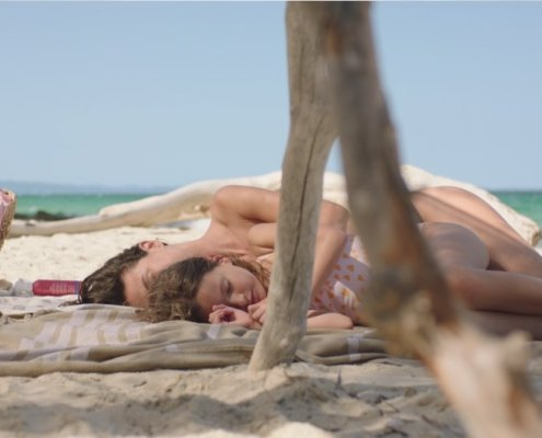mother and daughter lying on a beach